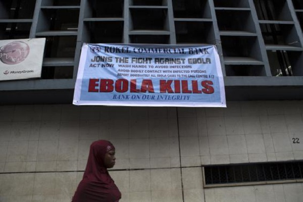 A woman passes a sign posted in an awareness campaign against the spread of Ebola in Freetown, Sierra Leone September 18, 2014 in a handout photo provided by UNICEF.