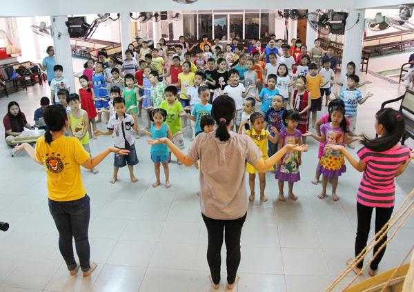 Các anh chị tập múa hát cho các em.