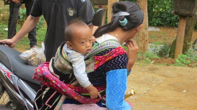 Thiếu nữ Mông địu con đi chợ phiên Sin Suối Hồ