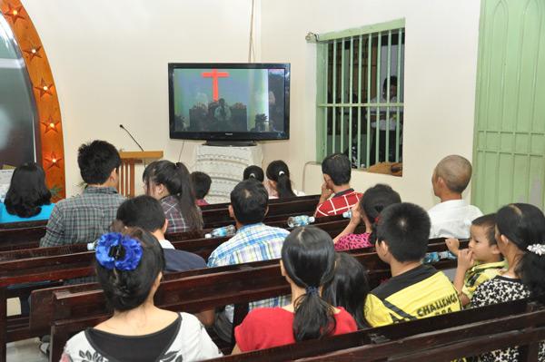 Các tín hữu ngồi xem trực tiếp chương trình qua TV tại một căn phòng khác