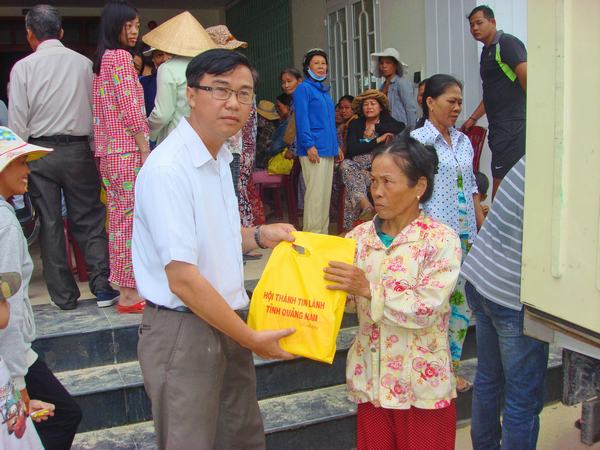 Mục sư Nhiệm chức Bùi Hùng - Quản nhiệm Hội Thánh Phong Thử, tỉnh Quảng Nam phát quà và thuốc men cho người dân