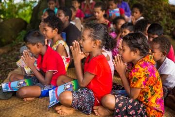 Các em nhỏ nhóm lại dưới tán xoài nghe kể về Đấng Christ.