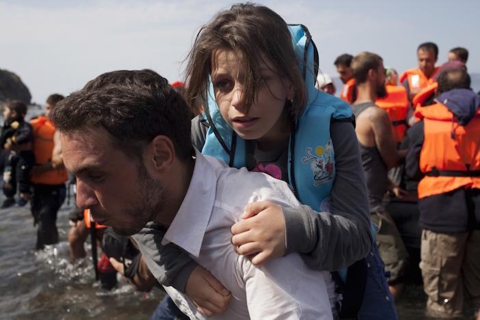 Một người đàn ông Syria cõng bé gái xuống thuyền sau khi cập bến một hòn đảo thuộc khu vực Lesbos của Hy Lạp.
