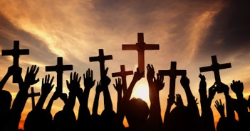 Group of People Holding Cross and Praying in Back Lit