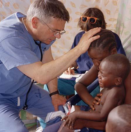 Một bác sĩ kiêm nhà truyền giáo cầu nguyện cho em nhỏ tại Sierra Leone.