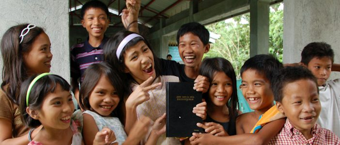 A group of kids hold up the Kinaray-a New Testament.