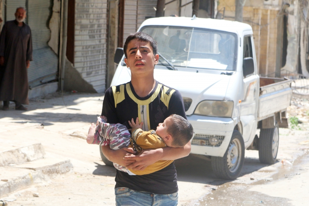 Một chàng trai bé em nhỏ chạy trốn khỏi cuộc oanh tạc tại quận al-Fardous, Aleppo vào ngày 29/4 vừa qua.
