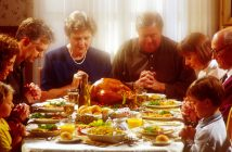 Family praying together over Thanksgiving dinner